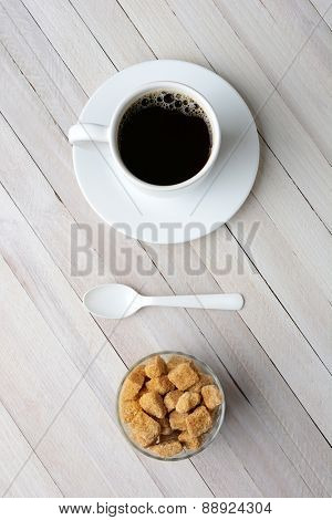 Overhead view of a cup of coffee, a bowl of natural sugar cubes and plastic white spoon. Vertical format on a rustic whitewashed table.