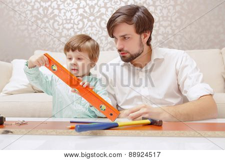 Father and son play with a toy building kit