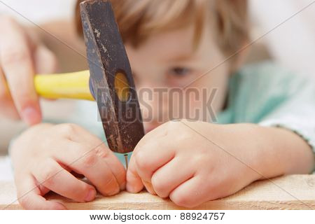 Small boy uses hammer