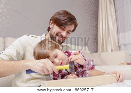Father and son use hammer