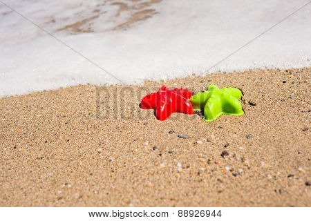 Red and green starfish-shaped molds on the sand