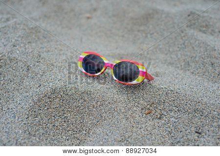 Children's striped sunglasses on the sand