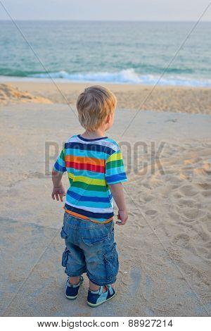 Little boy standing on the beach on sunset