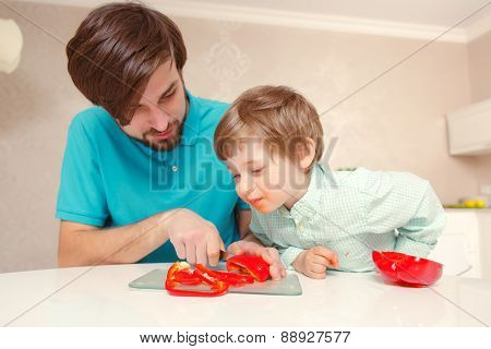 Father and son cook pepper
