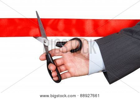 Businessman In Suit Cutting Red Ribbon With Pair Of Scissors Isolated On White Background