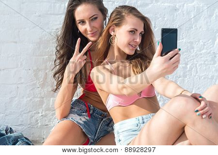 Female friends taking self-portrait picture photos with mobile smart phone showing gesture v victory
