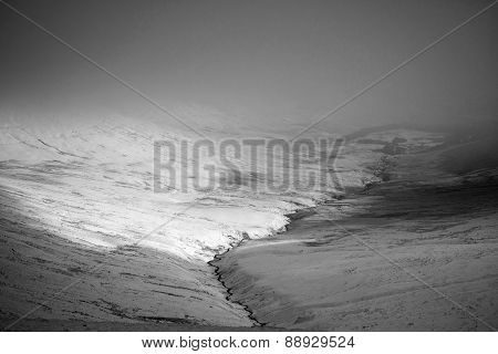 Moody Dramatic Low Cloud Winter Landscape In Mountains Valley In Black And White