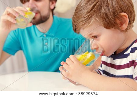 Father and son drink lemonade