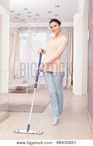 Woman mopping floor in living room