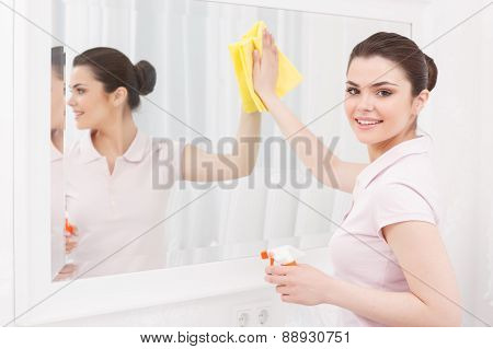 Beautiful lady cleaning mirror