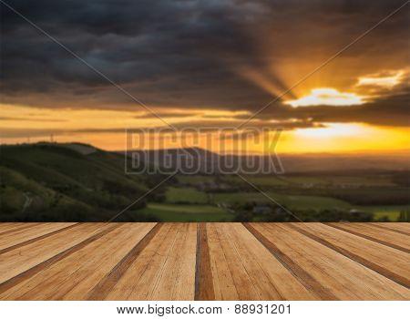 Stunning Vibrant Summer Sunset Over Escarpemt Landscape With Wooden Planks Floor