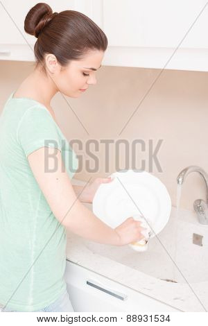 Woman doing washing up in kitchen