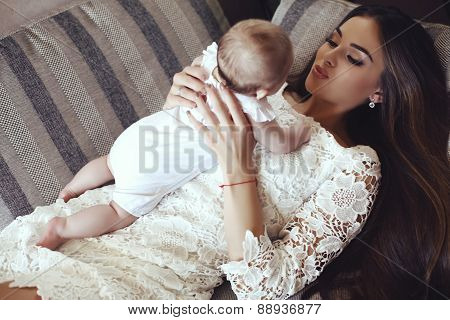 Beautiful Young Mother With Long Dark Hair Posing With Her Little Adorable Baby