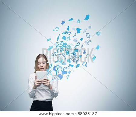 Beautiful Young Business Woman Is Looking At The Tablet. Flying Out Social Media Icons.