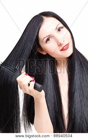 Portrait of a beautiful young woman combing her long groomed hair