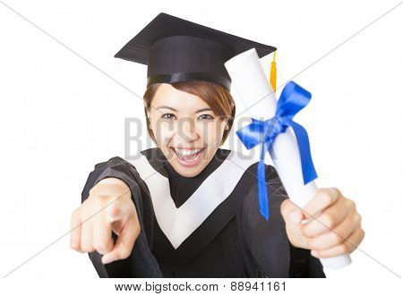 Happy Young Woman Graduating And Pointing To Camera
