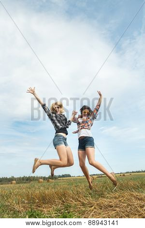 Freeze frame photography captures happy jumping of two friends