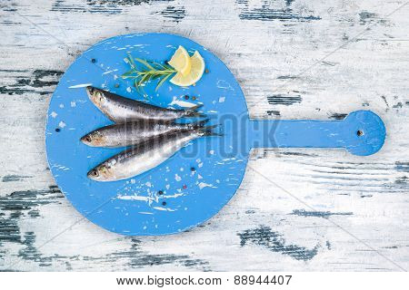 Fresh Anchovy Fish On White And Blue Wooden Kitchen Board.
