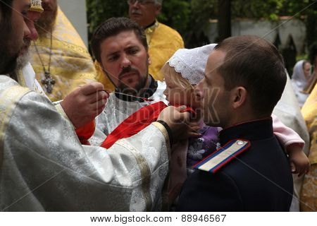 PRAGUE, CZECH REPUBLIC - MAY 28, 2012: Young girl receives the Eucharist during an orthodox service in front of the Dormition Church at the Olsany Cemetery in Prague, Czech Republic.