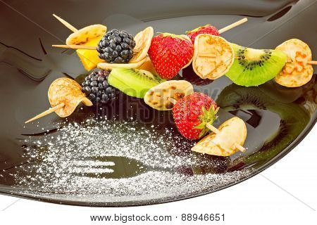 Fruit, Berries And Mini Blini Kebab On Black Plate, Dusted With Sugar Powder