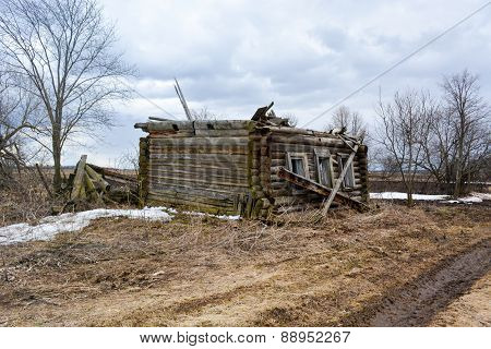 Collapsed wooden house without a roof in the countryside