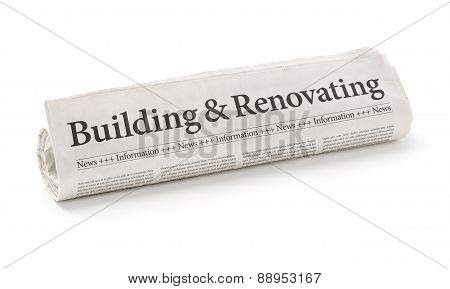 Rolled Newspaper With The Headline Building And Renovating