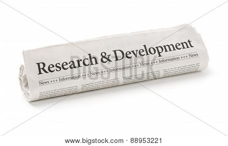 Rolled Newspaper With The Headline Research And Development