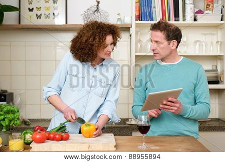 Husband And Wife Reading Recipe From Tablet
