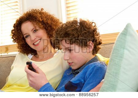 Cheerful Mother Sitting With Son Playing Games On His Phone