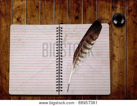 Open notebook and feather with ink bottle