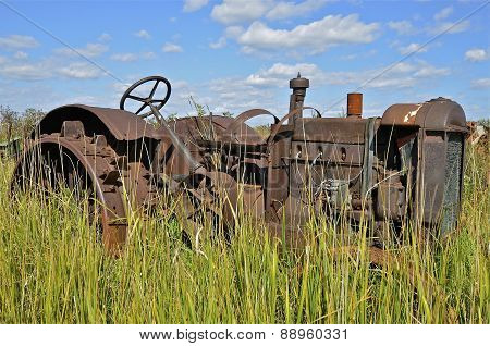 Rusty old tractor with steel wheels and lugs