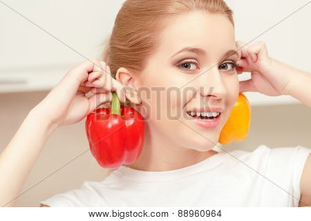 Young woman smiling and holding pepper