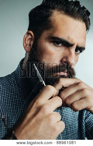 Man Grooming His Beard With Scissors