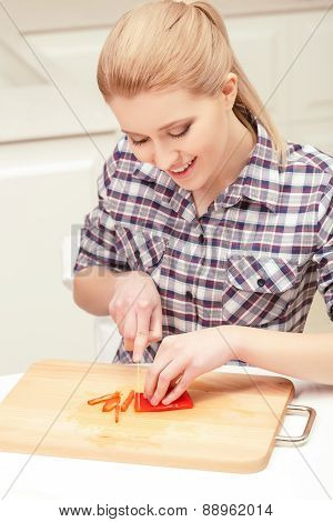 Pretty woman slices red pepper