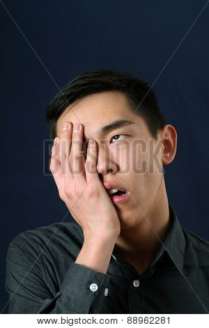 Young Asian man showing facepalm and rolling eyes up