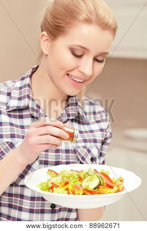 Young woman cooks salad