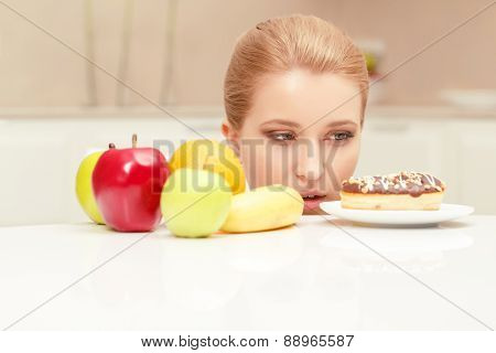 Woman looks at donut and wants to eat it