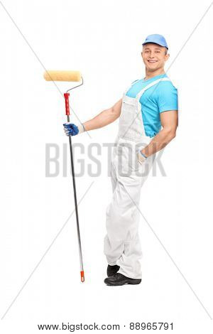 Full length portrait of a relaxed young painter in a white jumpsuit holding a paint roller and leaning against a wall isolated on white background