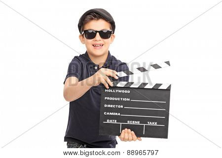 Little boy with sunglasses and a black beret having fun with a movie clapperboard isolated on white background