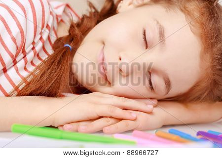 Lying little girl on desk