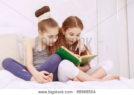 Pair of little girls reading book