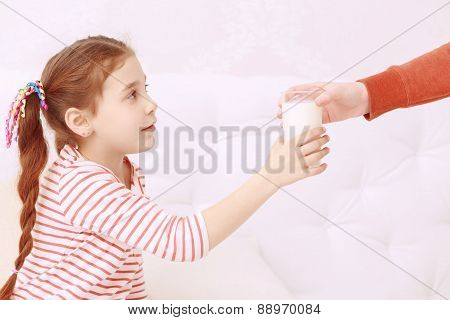 Little girl getting glass of milk