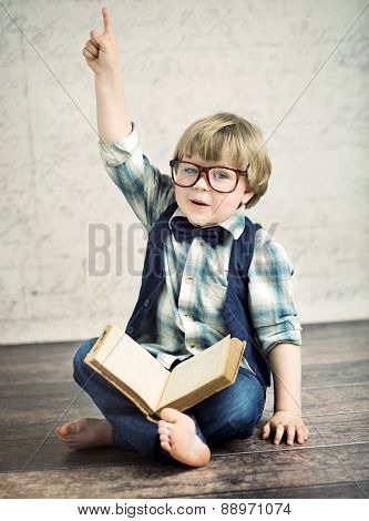 Cheerful smiling little kid with a book