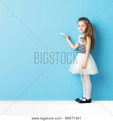 Girl drawing on blue chalkboard