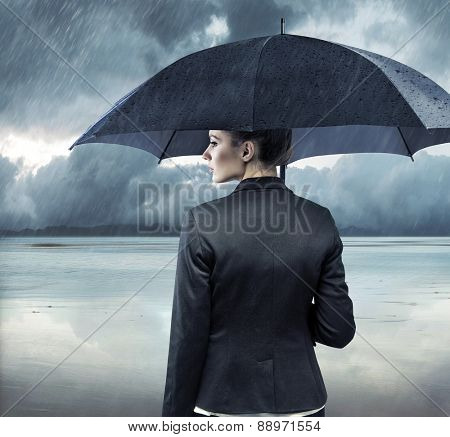 Businesswoman standing with an umbrella