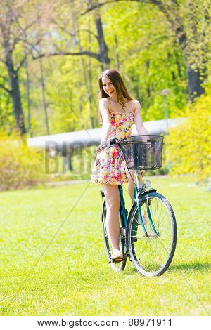Young woman in short colorful dress with long hair rides a bicycle tour summer city park, look and laughs to camera colour