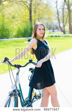 Young woman in short black dress with long hair rides a bicycle tour summer city park, look to camera