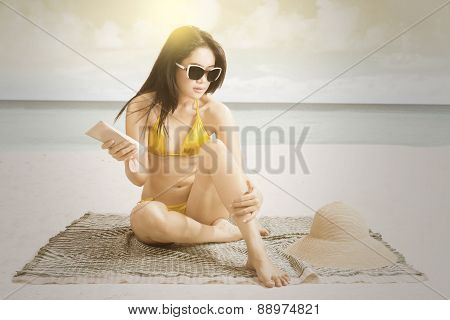 Girl Applying Sunblock At Seaside