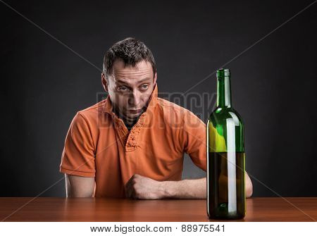 Drunk man looks at the bottle