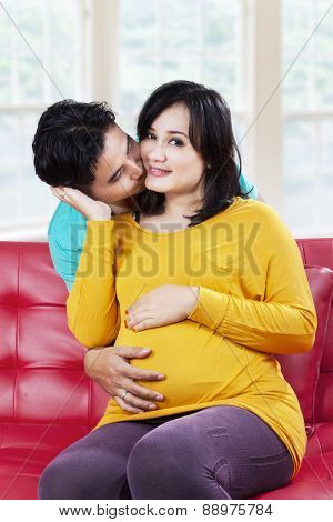 Happy Expectant Mother Kissed By Her Husband